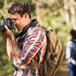 Young man taking photos during hiking — Stock Photo #49816693