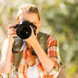 Woman taking photos in forest — Stock Photo #49818147
