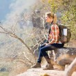 Woman sitting on the edge of cliff — Stock Photo #49819037