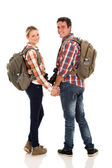 Couple with backpacks looking back — Stok fotoğraf