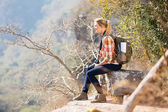 Woman sitting on the edge of cliff — Stockfoto
