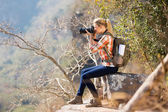 Woman taking photos by edge of cliff — Stok fotoğraf