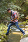 Photographer crossing stream — Stock Photo