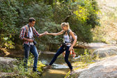 Man helping girlfriend crossing stream — Stock Photo