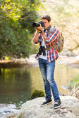 Man taking photos in mountain valley — Stock Photo