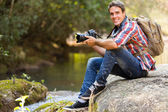 Photographer resting in mountain valley — Stock Photo