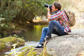 Photographer photographing in mountain valley — Stok fotoğraf