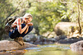 Young hiker drinking stream water — Stock Photo