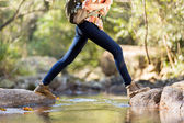 Young hiker crossing stream in mountain — Stock Photo
