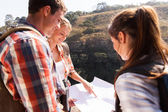Hikers on mountain pointing at map — Stock Photo