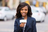 Female african news reporter working outdoors — Stock Photo