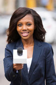 African news reporter interviewing with microphone — Stock Photo