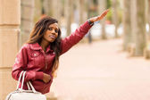 African woman hailing a taxi cab — Stock Photo