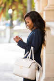 Young african woman using smart phone — Stock Photo