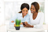 African mother and daughter using smart phone — Stock Photo