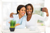 Middle aged african mother and daughter taking self portrait — Stock Photo