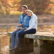 Young man and girlfriend fishing on pier — Stock Photo #50610521