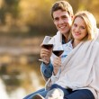 Young couple snuggle outdoors with glass of wine — Stok fotoğraf