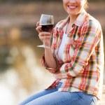 Beautiful young woman drinking wine on lake pier — Stock Photo #50614045