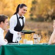 Waitress pouring wine for romantic couple — Stock Photo