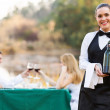 Waitress holding a bottle of wine in front of customers — Stock fotografie