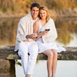 Couple sitting on pier and drinking wine — Stock Photo #50614621