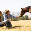 Cowboy and cowgirl playing with foal — Photo