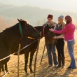 Group of friends petting horses — Stock Photo #50617525
