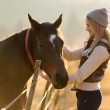 Woman petting horse in the farm — Stock Photo