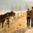 Young couple walking in the horse farm — Stock Photo #50619739