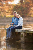 Young man and girlfriend fishing on pier — Stock Photo