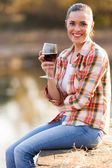 Beautiful young woman drinking wine on lake pier — Stock Photo