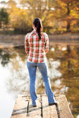 Back view of young woman standing on lake pier — Stock Photo