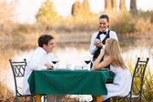 Young couple place dinner order to waitress — Stock Photo