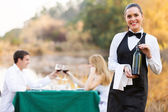Waitress holding a bottle of wine in front of customers — Stock Photo