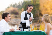 Female waitress taking order from young couple — Stock Photo