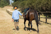 Cowboy walking with his horse — Stock Photo