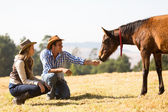 Cowboy and cowgirl playing with foal — Stock Photo