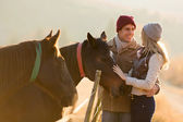 Young couple petting a horse in a paddock — Stock Photo