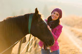 Young woman standing next to a horse — Stock Photo