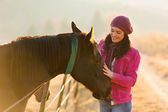 Woman touching horse in the paddock — Stock Photo