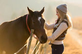Woman petting horse in the farm — Foto de Stock