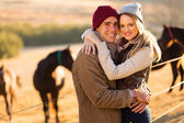 Happy young couple in horse ranch — Stock Photo