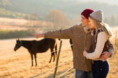 Young couple pointing at horse in the ranch — Stock Photo
