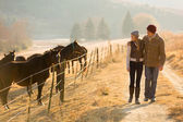 Young couple walking in the horse farm — Foto Stock