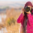 Young woman photographing in autumn — Stock Photo #50626053
