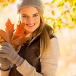Woman holding bunch of autumn leaves — Stock Photo #50627735