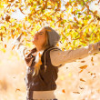 Autumn leaves falling on happy young woman — Stock Photo #50627949