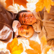 Underneath view of young couple holding autumn leaves — Stock Photo #50629665