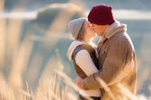 Young couple kissing by the lake in winter morning — Stock Photo